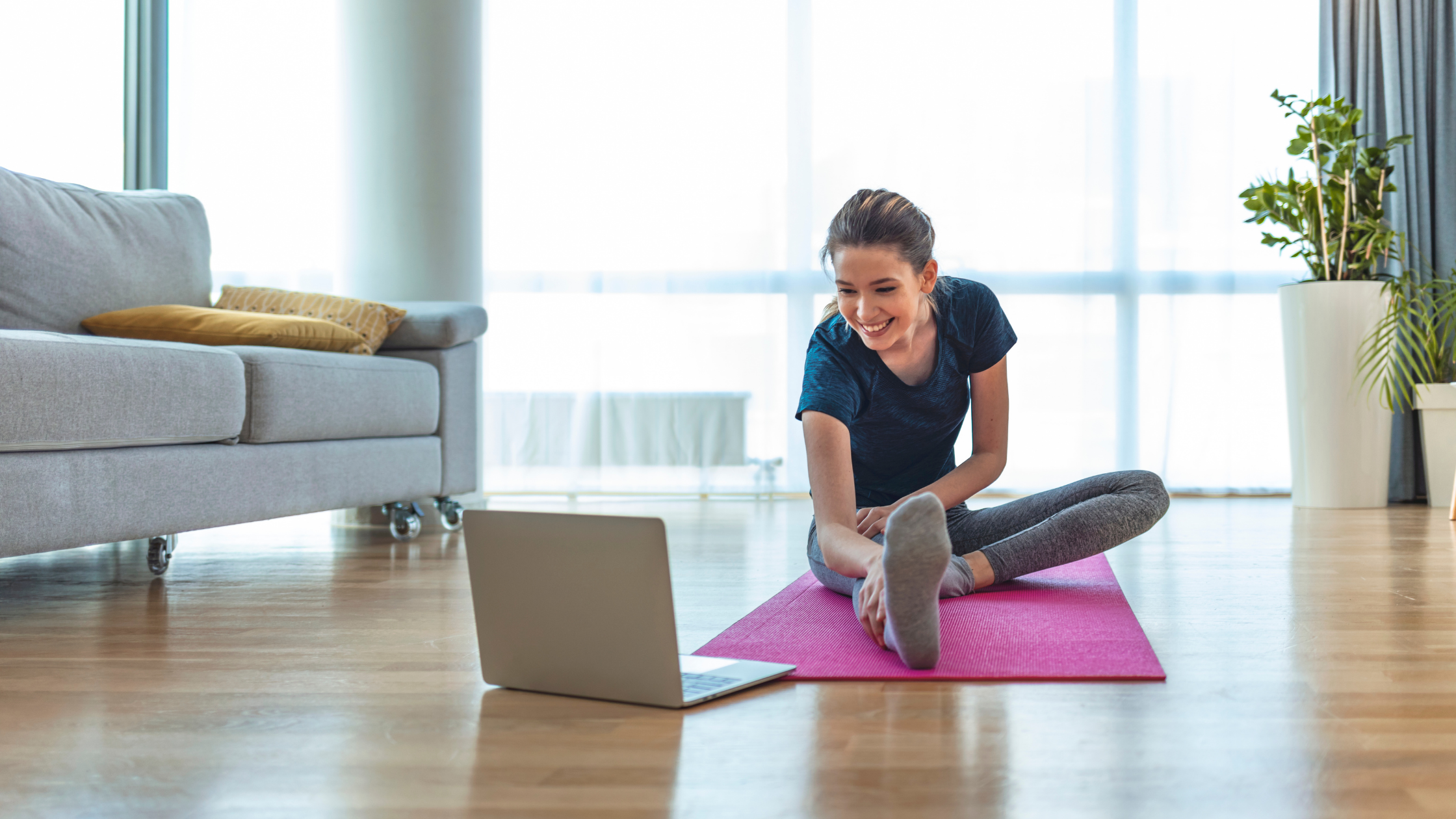 Woman smiling while working out at home on yoga mat