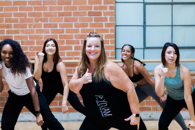 Dance fitness class smiling while listening to music